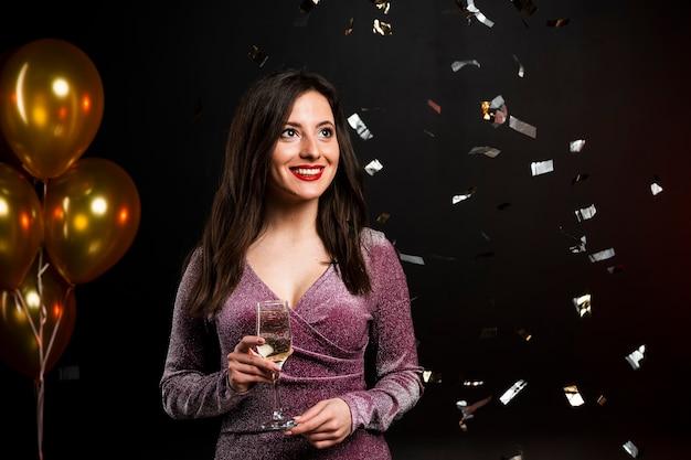 Donna che posa con il bicchiere di champagne e coriandoli alla festa