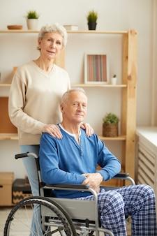 Donna che posa con il marito in sedia a rotelle