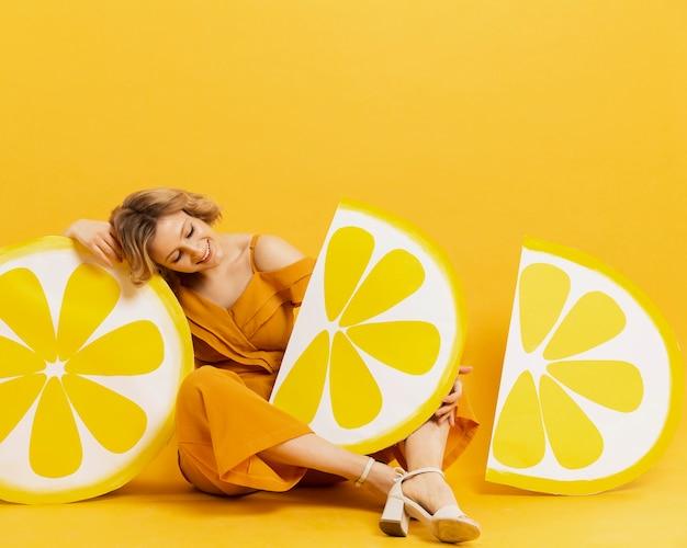 Donna che posa con la decorazione delle fette del limone e lo spazio della copia