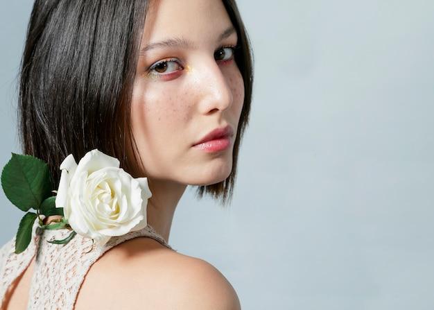 Donna che posa con la rosa bianca