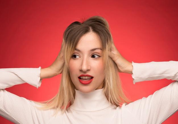Donna che posa con le mani sopra le orecchie