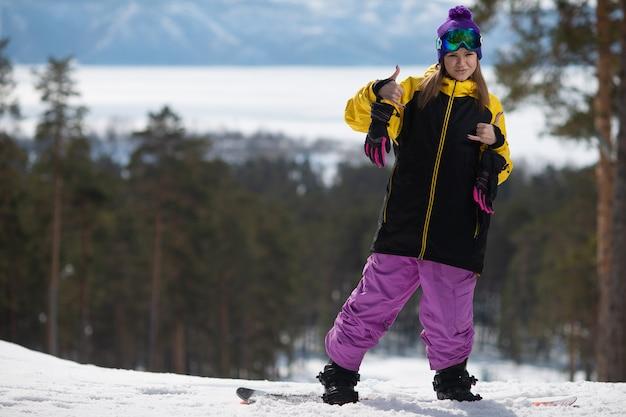 Donna che posa su uno snowboard