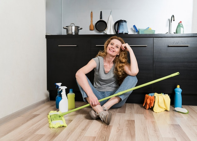 Donna che posa tenendo la scopa