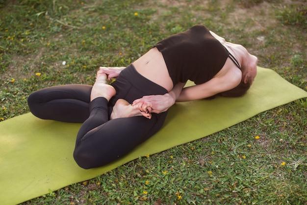 Donna che pratica all'aperto meditando nella posizione di yoga.