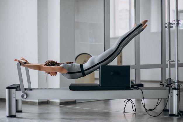 Donna che pratica pilates in un riformatore di pilates