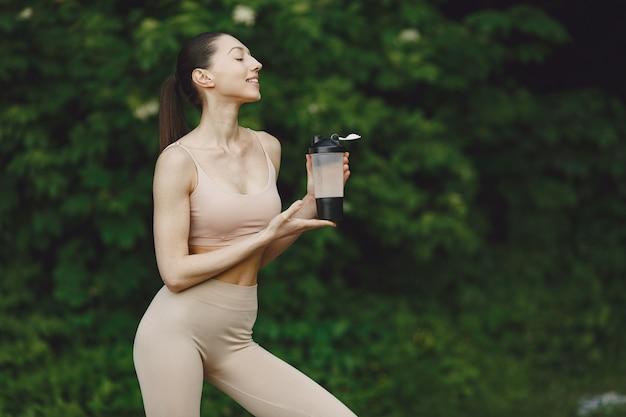Donna che pratica yoga avanzata in un parco estivo