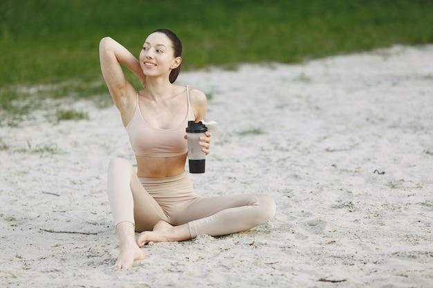 Donna che pratica yoga avanzata su una spiaggia estiva