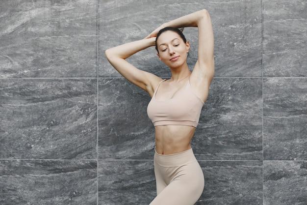 Donna che pratica yoga avanzato contro un muro urbano scuro
