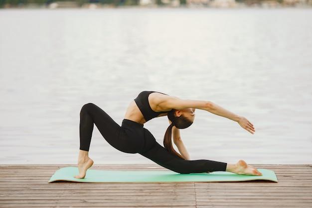 Donna che pratica yoga avanzato dall'acqua