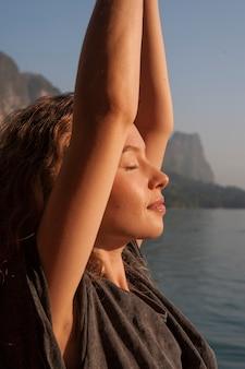 Donna che pratica yoga da un lago