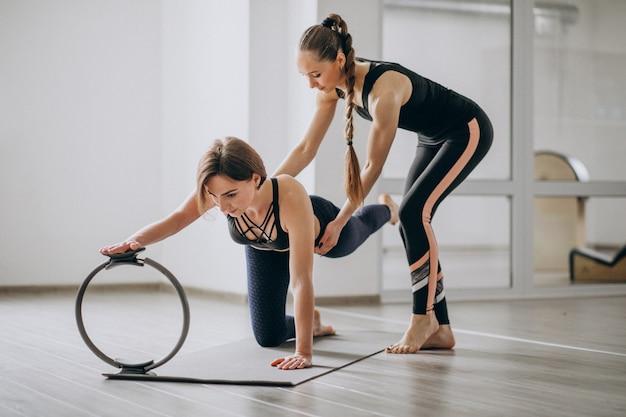 Donna che pratica yoga in palestra con l'allenatore