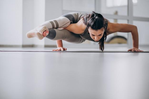 Donna che pratica yoga in palestra su una stuoia