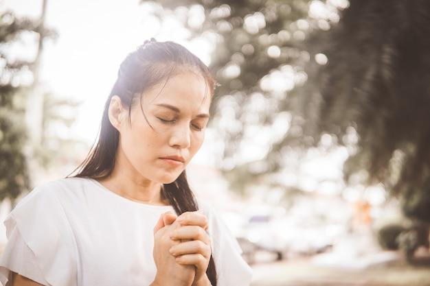 Donna che prega a dio nel giardino al mattino.
