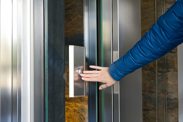 Donna che preme il pulsante del moderno ascensore in vetro.