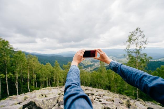Donna che prende foto con lo smartphone nella natura
