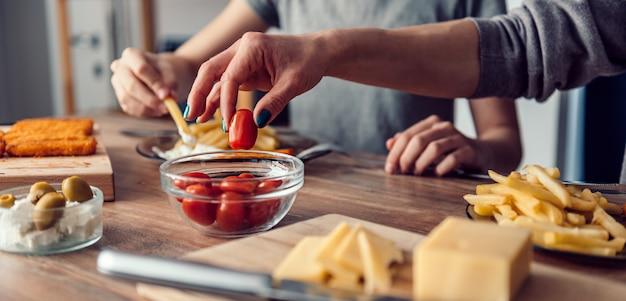 Donna che prende il pomodoro ciliegia da un piatto sulla tavola