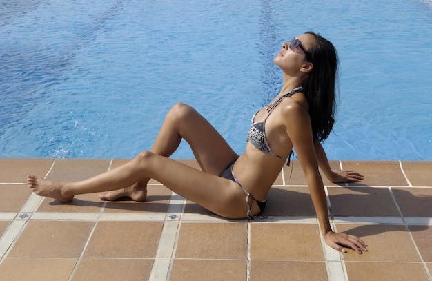 Donna che prende il sole in piscina