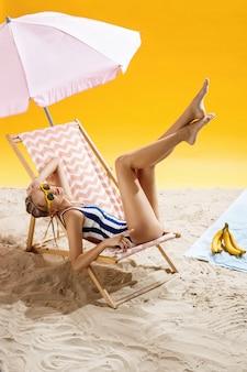 Donna che prende il sole sotto l'ombrello alla bella spiaggia e che gode del momento