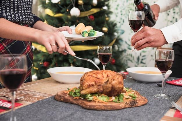 Donna che prende pollo al forno dal tavolo festivo