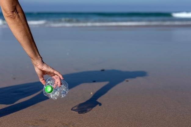 Donna che prende spazzatura e materie plastiche che puliscono la spiaggia