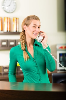 Donna che prende una chiamata alla reception della palestra