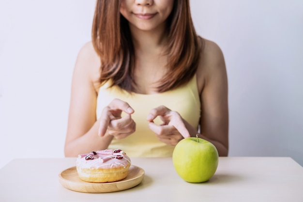 Donna che prende una decisione tra cibo sano e cibo malsano, concetto di stile di vita sano e dieta