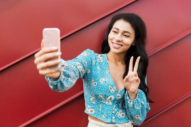 Donna che prende una foto di auto e che mostra il segno di pace