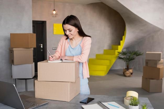 Donna che prepara scatole da casa per la consegna