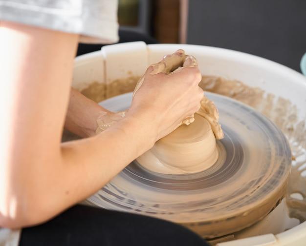 Donna che produce ceramica su ruota, creazione di ceramica. concetto di lavoro femminile, artigianato