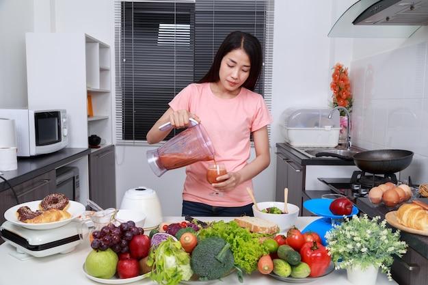 Donna che produce frullati con blender in cucina