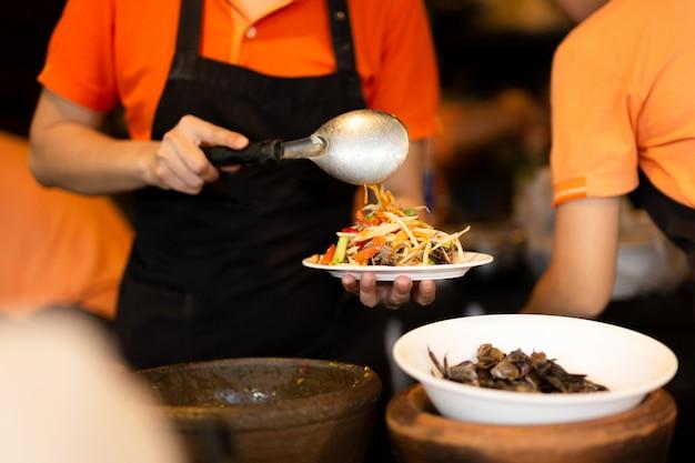 Donna che produce l'insalata piccante della papaia della tailandia con il granchio in ristorante.