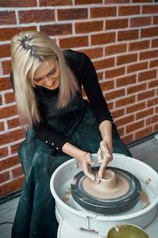 Donna che produce terraglie ceramiche sulla ruota. concetto per donna freelance, affari. prodotto artigianale