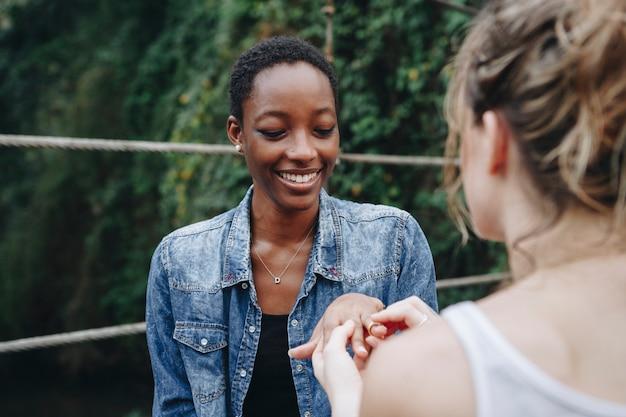 Donna che propone alla sua amica felice all'aperto amore e concetto di matrimonio