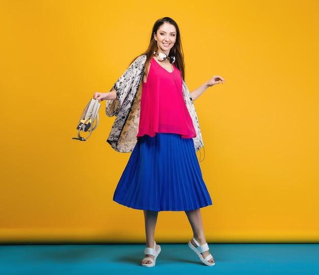 Donna che propone in moda estiva alla moda e borsa umore colorato