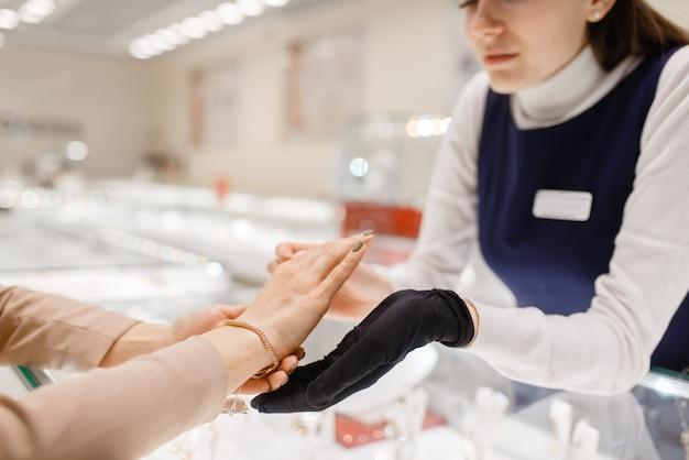 Donna che prova il braccialetto d'oro in gioielleria