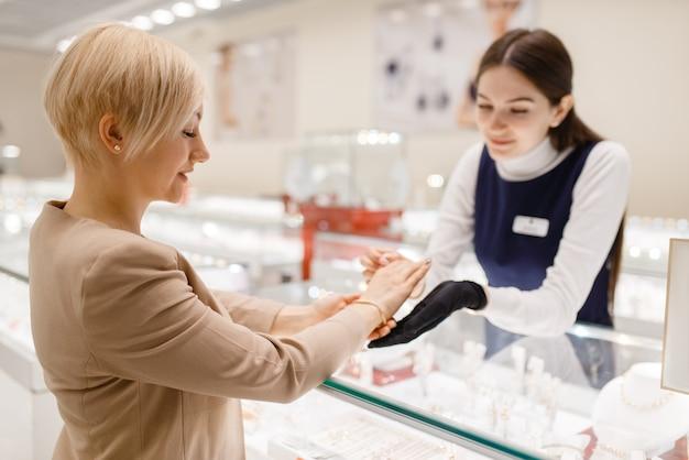 Donna che prova il braccialetto dell'oro alla vetrina in gioielleria