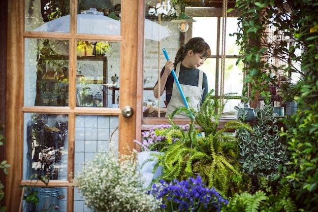 Donna che pulisce dentro il suo negozio di fiori