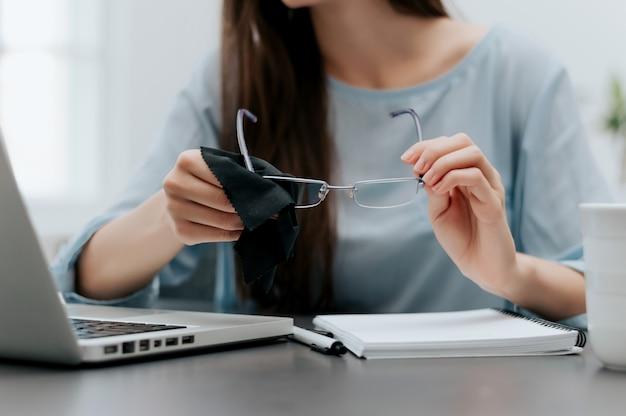 Donna che pulisce i suoi occhiali sul posto di lavoro.