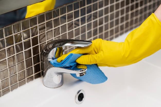 Donna che pulisce il lavandino del bagno
