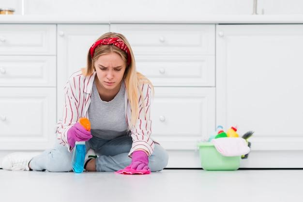 Donna che pulisce il pavimento con cura