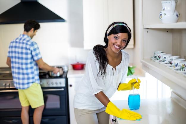 Donna che pulisce la cucina e l'uomo che cucina alimento nel fondo