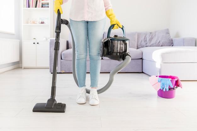 Donna che pulisce la sua casa con l'aspirapolvere