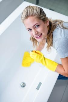 Donna che pulisce la vasca da bagno nel bagno