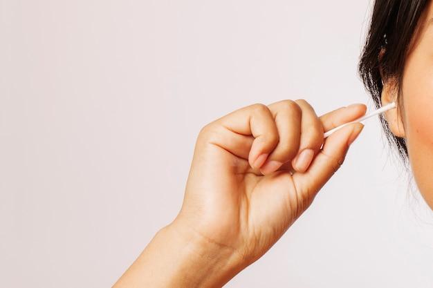 Donna che pulisce le orecchie con tamponi di cotone