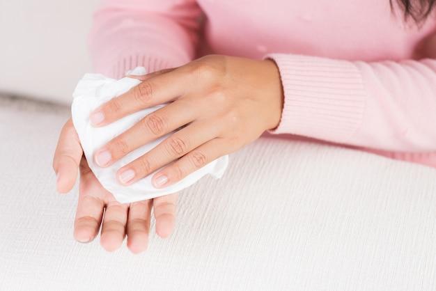 Donna che pulisce le sue mani con un fazzoletto. sanità e concetto medico.