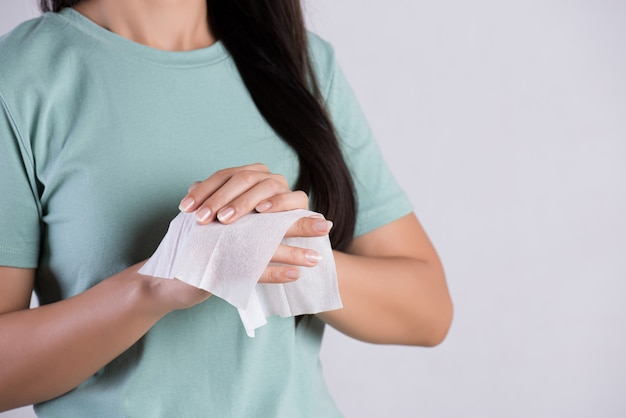 Donna che pulisce le sue mani con un tessuto. concetto di assistenza sanitaria e medica
