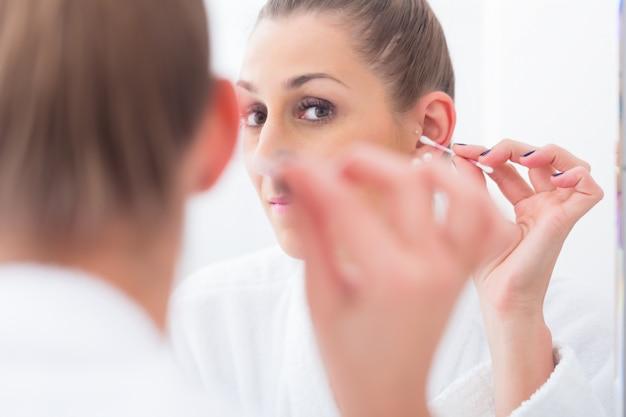 Donna che pulisce le sue orecchie con un batuffolo di cotone