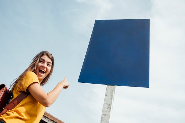 Donna che punta a un cartellone mock-up
