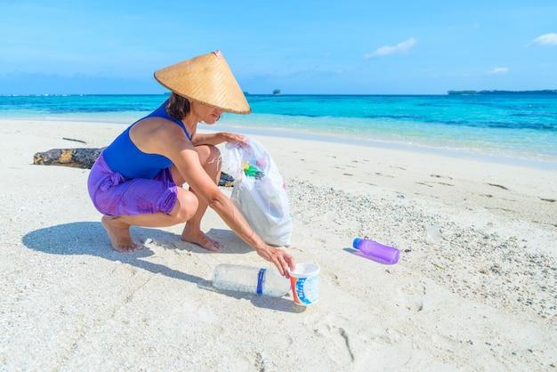 Donna che raccoglie bottiglie di plastica sulla bellissima spiaggia tropicale, mare turchese