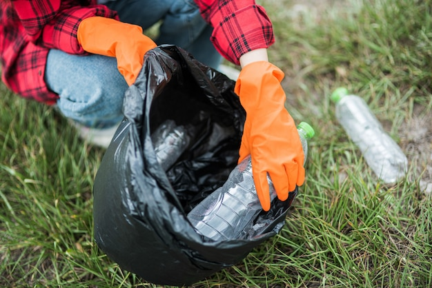 Donna che raccoglie immondizia in una borsa nera.